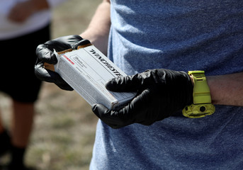 Firearms instructor Joseph Wilkey wears gloves while holding a box of 9mm Winchester ammunition during a firearms safety class conducted by Level Up Firearms outside Loveland