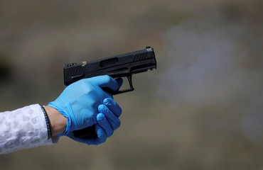 A woman is pictured with protective gloves as she shoots a handgun during a firearms safety class conducted by Level Up Firearms outside Loveland