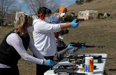 Firearms instructor Joseph Wilkey instructs a mother and her two teenage sons during a firearms safety class conducted by Level Up Firearms outside Loveland