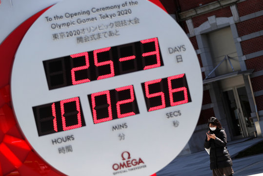 A woman wearing a protective face mask due to the outbreak of coronavirus disease (COVID 19) stands next to Omega clock for the Tokyo 2020 Olympic Games after the announcement of the games' postponement to the summer of 2021, in Tokyo