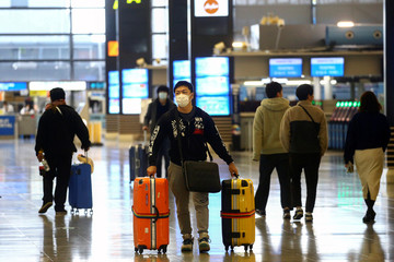 A passenger, wearing protective mask following an outbreak of the coronavirus disease (COVID-19), carry his baggage at Kansai International Airport in Osaka