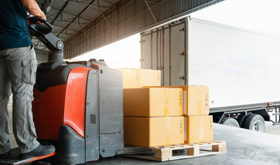 Forklift driver loading pallet shipment goods into a truck, package boxes, Road freight transport, Warehouse industrial delivery shipment and logistics