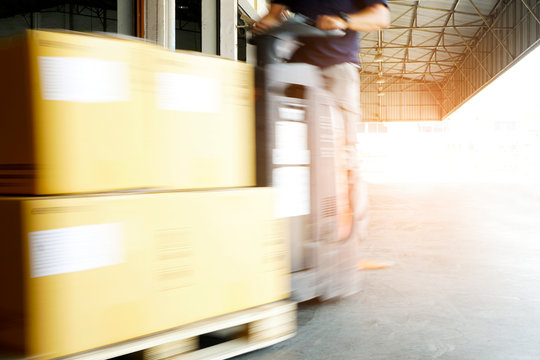 Speed motion blur of forklift driver loading pallet shipment goods, package boxes, warehouse industry delivery logistics