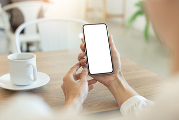 Mockup image blank white screen cell phone.woman hand holding texting using mobile on desk at...