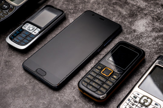 Many obsoleted cellphones and a smartphone on a grunge background.