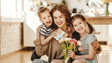 Happy children giving gift an flowers to mother.