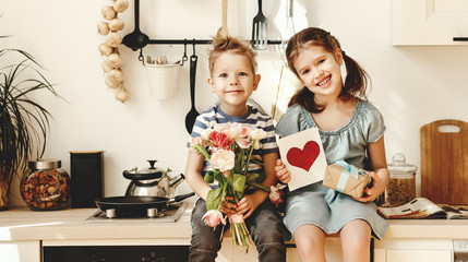 Little siblings with gift and flowers for mom sitting in kitchen Fototapete