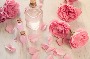 Foto op Plexiglas Spa Rose water or oil in glass bottles with pink fresh rose flowers and petals on wooden background, SPA concept and aromatherapy