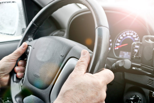 Men's hands on the steering wheel of a car. The driver controls the car.