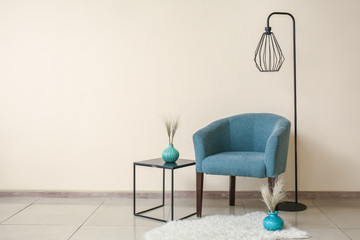 Comfortable armchair, table and lamp near color wall