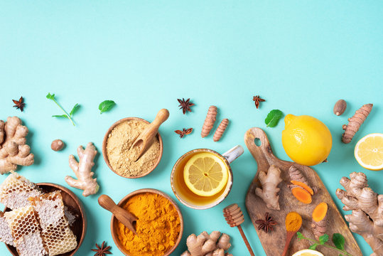 Spicy healthy turmeric drink with lemon, ginger, honey on blue background. Immune system booster food, antiviral beverage. Vegan hot drink concept.
