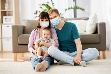 health, safety and pandemic concept - happy mother and father with baby wearing protective medical...