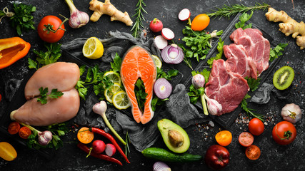 Protein Menu: Meat, Fresh Vegetables, Fruits, and Nuts. Healthy food on black stone background.