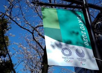 T campaign banner for the Tokyo 2020 Olympics and Paralympics is displayed under blooming cherry blossoms in Tokyo