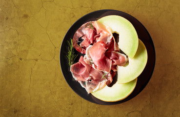 Fototapete - Prosciutto with rosemary and melon on a black plate.