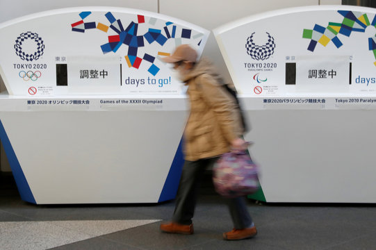 An elderly person wearing a protective face mask due to the outbreak of coronavirus disease (COVID 19) walks past countdown clocks for the opening of Tokyo 2020 Olympic and Paralympic Games in Tokyo