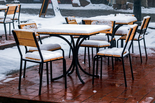 Snowy outdoor cafe.  Street chairs and tables covered with white fresh snow.