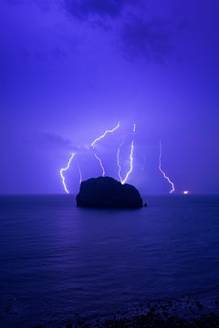 A bunch of thunders hitting a small island in the sea. Vertical photography with a lot of blue.