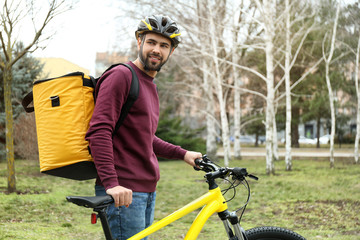 Courier with thermo bag and bicycle outdoors. Food delivery service