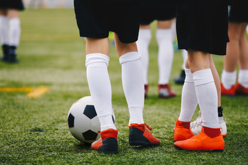 Soccer players with ball on a training field. Young junior level athletes in football cleats and uniforms on grass training ground. Closeup image of soccer players legs. Football background