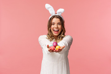 Holidays, spring and party concept. Portrait of lovely, romantic young blond woman in rabbit ears and white dress, giving you painted easter eggs as celebrating orthodox holiday, pink background