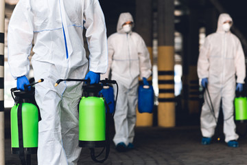 Men in virus protective suits carrying spray bottles with chemicals