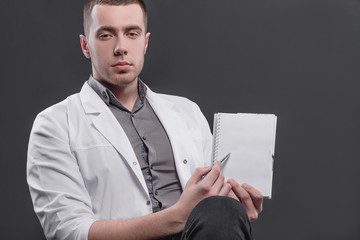 Young, pretty man in a medical coat on a gray background. The concept of medical education and medical activity