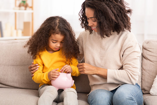 Little Girl Putting Money To Piggybank Sitting With Mother Indoor
