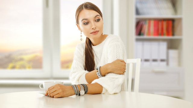 Slim young woman sitting in home interior and white wooden table of free space for your decoration.Blurred background of window.