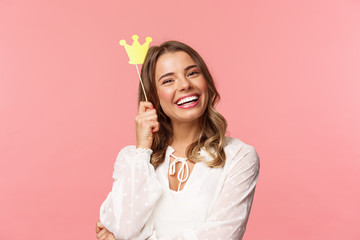 Spring, happiness and celebration concept. Close-up portrait of charming smiling, lovely blond girl holding small queen crown on stick, laughing joyfully, feel empowered and happy, pink background