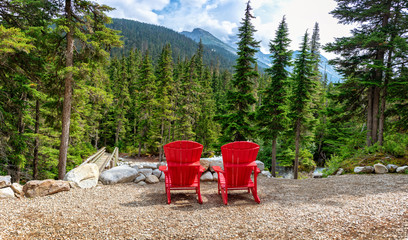 Two red wooden chairs with a view on the mountains in Glacier National park, Rocky Mountains, Bristish Columbia, Canada