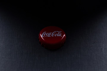 classic cap close-up of Coca-Cola on against a dark background