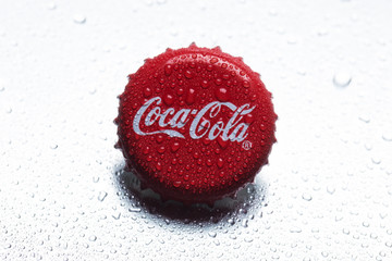 classic cap close-up of Coca-Cola on a gray background with drops of water.