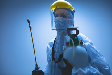 Scientist holding chemical sprayer for sterilization and decontamination of viruses, germs, pests,...
