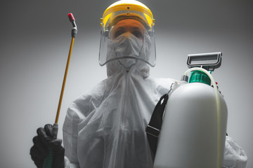 Scientist holding chemical sprayer for sterilization and decontamination of viruses, germs, pests, infectious diseases.