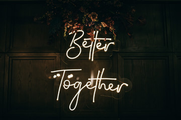 Better Together - neon sign on a brick wall in a restaurant at a wedding party. Love concept