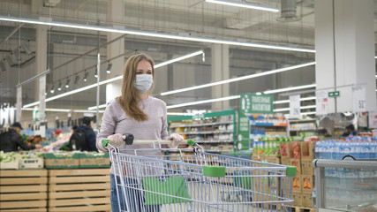 A sad woman in a medical mask and rubber gloves stands in a supermarket with a grocery cart and...