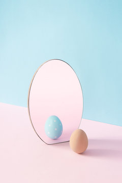 Creative Easter concept with egg and mirror on pastel pink and blue background. Minimal Easter Holiday idea.