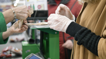 Woman at the supermarket checkout picks up change after shopping in rubber protective gloves....