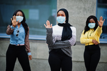 Group of three african american young volunteers wearing face mask outdoors. Coronavirus quarantine and global pandemic.