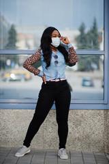 African american young volunteer woman wearing face mask outdoors. Coronavirus quarantine and global pandemic.