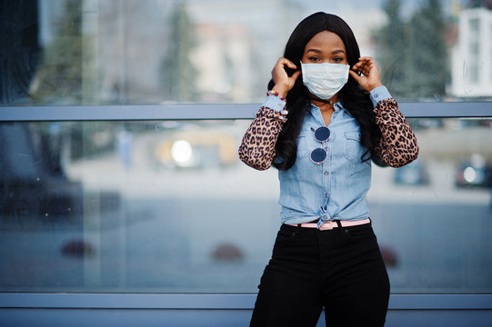 African american young volunteer woman wearing face mask outdoors. Coronavirus quarantine and global pandemic.