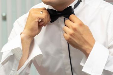 The groom straightens a bow-tie on a shirt close-up