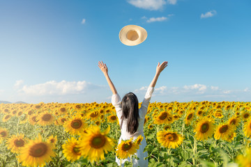 Tuinposter Zonnebloem happy young and long hair asian woman in the field of sunflowers, standing arm raised throwing hats.