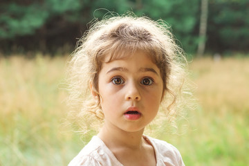 Close up Portrait of beautiful little Girl  surprised with something at summer day Fototapete