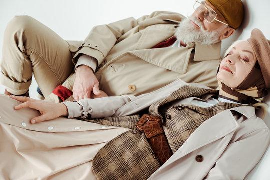 Elegant senior couple in trench coats lying on white background