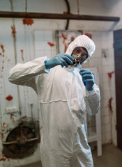 Fototapeta Scientist doctor biologist in hazmat suit and protective respiratory mask working in laboratory with test tubes searching vaccine against Coronavirus COVID-19