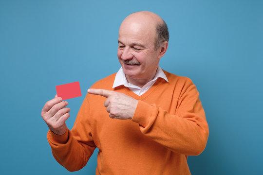 Happy senior hispanic bald man advertising bonus card smiling at camera.