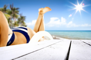 White desk of free space for your product and blurred background of beach with slim young woman body in bikini.