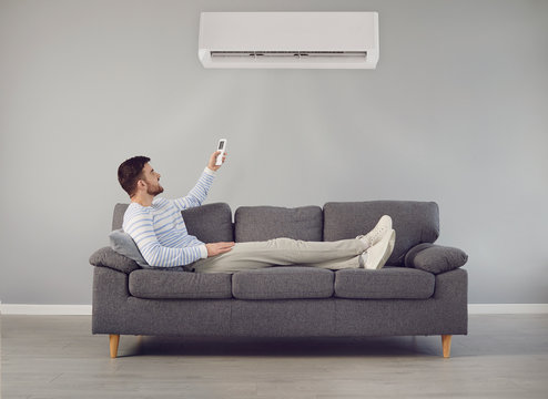 The young man turns on the air conditioner cools the air while sitting on the sofa in the room